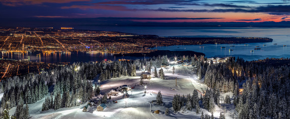 Skiing on the illuminated ski slopes of Grouse Mountain with a view of Vancouver City at Dusk