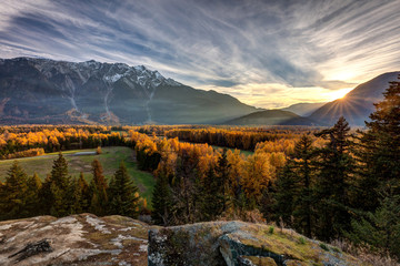 The sunshine giving a golden glow to the trees in Autumn with Mount Currie towering over the Pemberton Valley in British Columbia, Canada