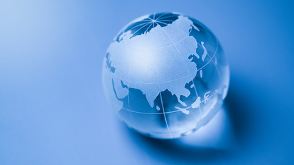 World glass globe on blue background with focus asia