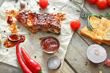 Tasty grilled meat with barbecue sauce, vegetables and spices on table