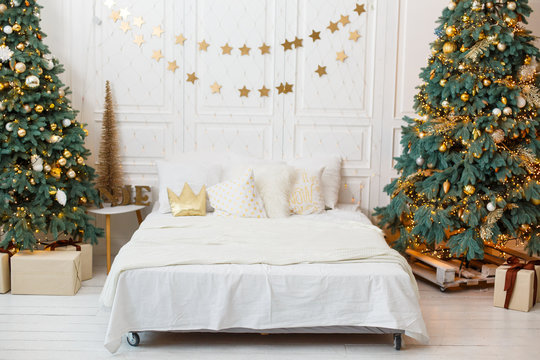 Romantic bedroom in light colors with a lot of garland lights decorated for New Year Celebrating. Christmas mood at home. White bedroom and Christmas spruces. Romantic interior. Breakfast in a bed