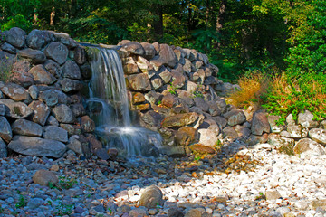 Long exposure image of a small, artificial waterfall cascading onto large stones at Duke Farms, New Jersey