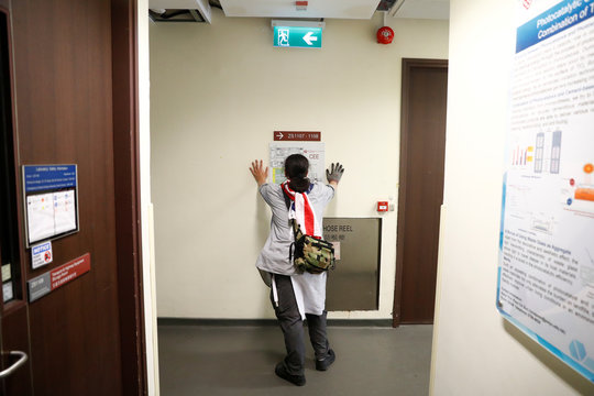 A protester looks at a floor plan of a building during a search for fellow protesters who might be hiding, at the Hong Kong Polytechnic University (PolyU)