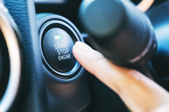 Closeup image of a finger pressing on a start stop engine button in a car