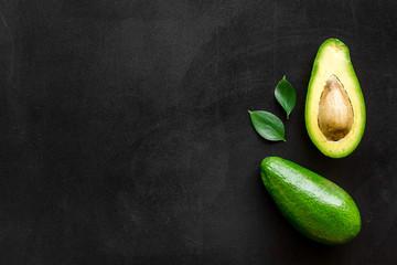 Foto op Plexiglas Keuken Avocado - whole and halfs - frame on black background top view copy space