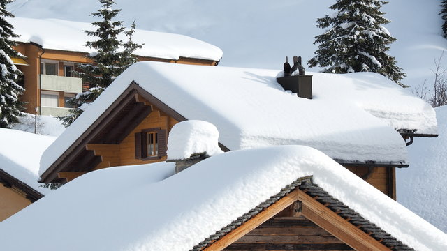 San Bernardino, Switzerland. The roofs of houses covered with fresh snow after heavy snowfall. Mountain and winter contest. Swiss alps