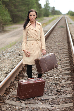 Woman with suitcase on the rails