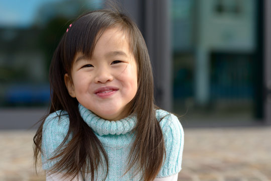 Friendly little Asian girl with a playful smile