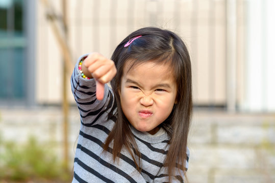Angry little Asian girl punching at the camera