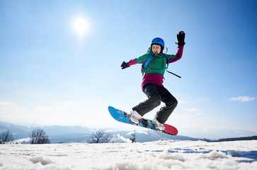 Sportive young woman snowboarder making dangerous jump in air on copy space background of clear bright blue sky and snowy mountains. Winter sports and recreation, leisure outdoor activities concept.