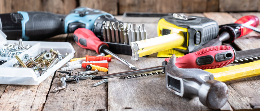 Piles of different sizes, types and colors in transparent plastic organizer box with other carpentry tools such screw driver, cordless drill measuring tape and hand saw on old wooden background.