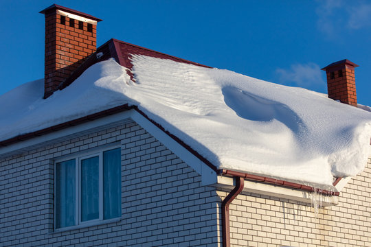 Brick house with snow on the roof