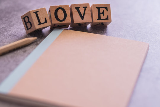 Sharp pencil and notebook with LOVE cube word . Concept for love story or letter or message, togetherness of friendship or family or couple or lover, wedding inviation. Be my romantic Valentine.