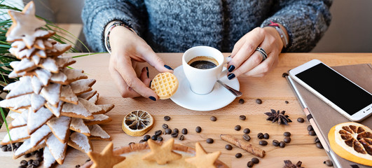 Espresso in white cup  in woman's hands with handmade cookie and smartphone on a wooden table in...