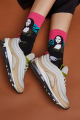 Cropped shot of a girl's foots in white sneakers, lying on a brown background. It is black artwork socks with Mona Lisa print on foots.