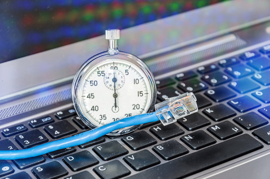 Cable and stopwatch on computer keyboard symbolizing bandwidth of internet connection