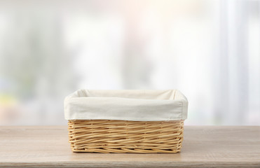 Straw empty basket with white linen on table.