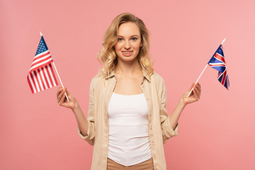 Attractive blond woman holding american and Britain flags isolated on pink