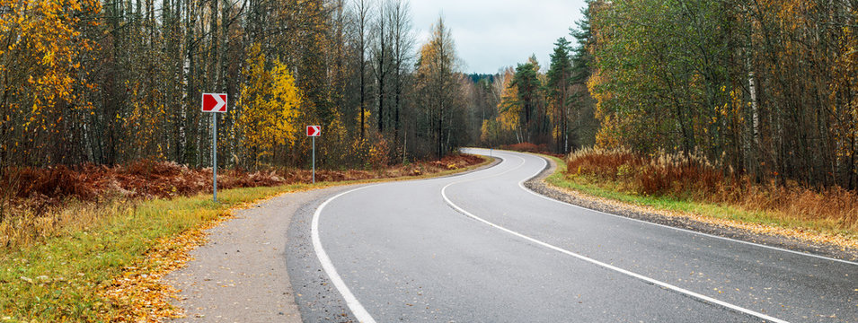 panorama winding asphalt road through the autumn forest without cars