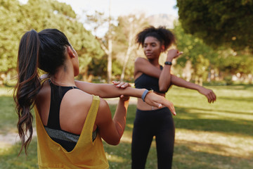 Two sporty fitness young diverse female friends stretching their muscles in park on a summers day - two friends working out together