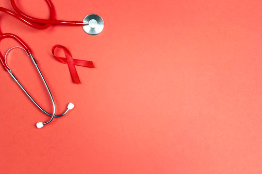 Red ribbon as symbol of aids awareness with stethoscope on red background. 1 december World Aids Day concept.