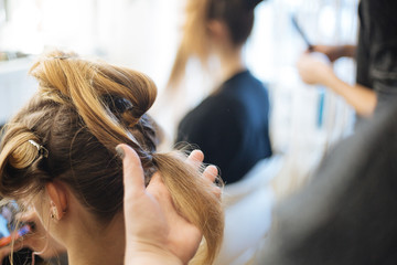 Hairdresser does wedding hairstyle for bride.