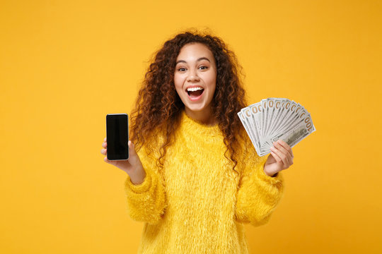 Excited young african american girl posing isolated on yellow background. People lifestyle concept. Mock up copy space. Hold mobile phone with blank empty screen fan of cash money in dollar banknotes.
