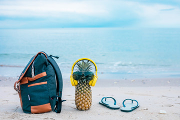 Cook the attractive pineapple in stylish sunglasses, golden bags and headphones in the sand with turquoise water. Tropical summer holiday concept