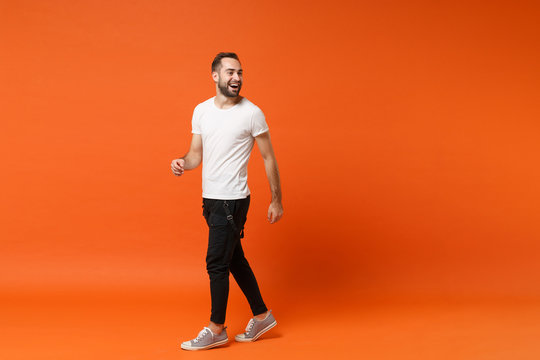 Cheerful laughing young man in casual white t-shirt posing isolated on bright orange wall background studio portrait. People sincere emotions lifestyle concept. Mock up copy space. Looking aside.