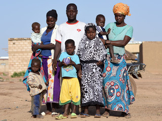 Zakaria Sawadogo poses for a photograph with family members in Kamboinse, a northern district of Ouagadougou, Burkina Faso