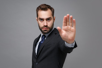 Serious young bearded business man in classic black suit shirt tie posing isolated on grey background. Achievement career wealth business concept. Mock up copy space. Showing stop gesture with palm. Wall mural