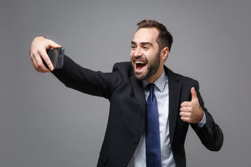 Cheerful young business man in suit shirt tie posing isolated on grey background. Achievement career wealth business concept. Mock up copy space. Doing selfie shot on mobile phone, showing thumb up.
