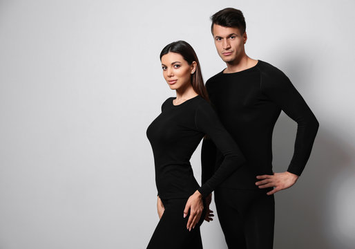 Couple wearing thermal underwear on light grey background. Space for text