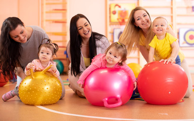 Group of mothers and their kids doing yoga exercises on gymnastic balls at fitness gym