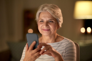 technology, communication and people concept - happy senior woman with smartphone at home in evening