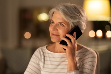 technology, communication and people concept - happy senior woman calling on smartphone at home in...