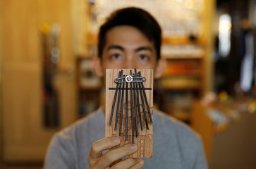 Kevin Cheung, an upcycling product designer, holds a thumb piano as he poses for a picture at his house in Hong Kong