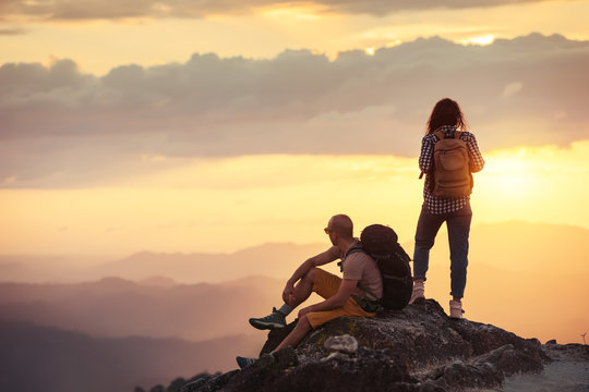 Couple hikers at sunset mountain viewpoint
