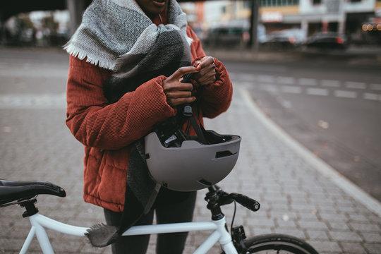Woman holding bicycle helmet
