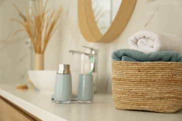 Fresh towels and toiletries on white countertop in bathroom