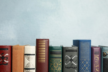 Collection of old books on light blue background. Space for text