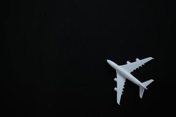 Miniature toy airplane white on black background.