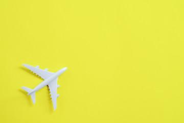 Miniature toy airplane white on yellow background.