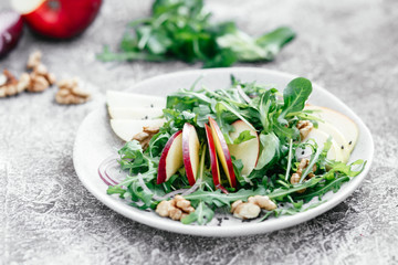 Vegetarian salad of fresh apples with arugula, onions and nuts in a plate on the table