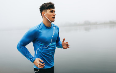 Horizontal outdoor image of young runner man running in the morning on the fog lake background....