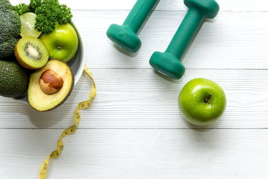 Healthy lifestyle for women diet with dumbbells sport equipment, sneakers, measuring tape, fruit healthy green apples and bottle of water on wooden.  Healthy Concept..