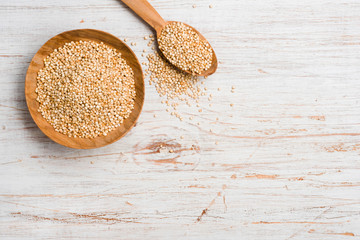 Quinoa seeds in wooden spoon and bowl on vintage background