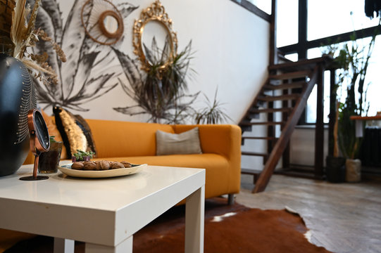 The concept of designing a room in a natural style. Photo of a beautifully furnished interior with a bright sofa in a rustic image of a cozy house.