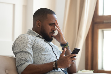 Frustrated african American man disappointed by bad message