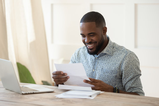 Smiling biracial male receive good news in postal correspondence